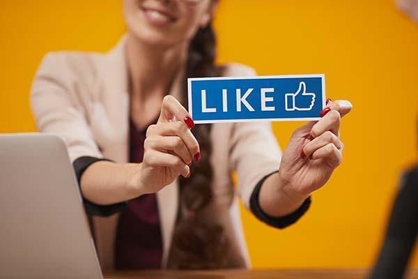 woman holding a social media like icon